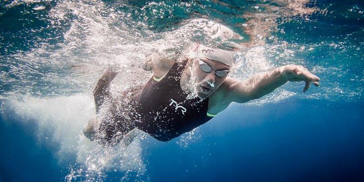 Чтобы стать хорошим пловцом, недостаточно отточить движения и освоить разные стили плавания. Первое, чему нужно научиться – правильно дышать. Без постановки техники дыхания все труды по обучению могут свестись на нет. Поэтому внимательно слушайте рекомендации тренера во время занятий, а если учитесь самостоятельно, изучите полезные статьи о постановке техники дыхания. Помните, что правильно дышать нужно независимо от того, занимаетесь вы плаванием на открытой воде или ходите в бассейн. Зачем вообще это необходимо Правильная постановка дыхания имеет огромное значение. Вот только несколько факторов, на которые она влияет: скорость в освоении разных стилей плавания; уровень выносливости во время заплыва; координация спортсмена в воздушно-водном пространстве и правильное положение тела на воде; распределение нагрузки на сердечно-сосудистую, дыхательную систему, опорно-двигательный аппарат; показатели эффективности занятий и личный результат пловца; комфорт спортсмена – если он дышит правильно, ему легче и удобнее во время тренировки. Это весьма убедительные аргументы, которые доказывают значимость дыхания во время плавания. А теперь перейдем непосредственно к рекомендациям по его постановке. Общие правила В каждом стиле свои требования к тому, как нужно дышать. Но есть и общие аспекты, которые учитывают в любом из них: выдох всегда делается в воду; вдыхают только ртом, а выдыхают через нос и рот; дышать необходимо более интенсивно, чем в спокойном состоянии. Это обусловлено тем, что вода давит на грудную клетку, поэтому вдыхать нужно на полную силу; важно соблюдать ритмические вдохи-выдохи, без пауз. Задерживать дыхание нельзя, так как это сбивает весь процесс. И главное: пловец должен на отлично выполнять технику движений. Только в таком случае получится достичь скоординированной работы всего тела. Для «кроля» Если вы плаваете в этом стиле, будут полезны такие рекомендации: Синхронизация вдохов-выдохов происходит одновременно с движением рук. Вдыхаете вы в момент гребк